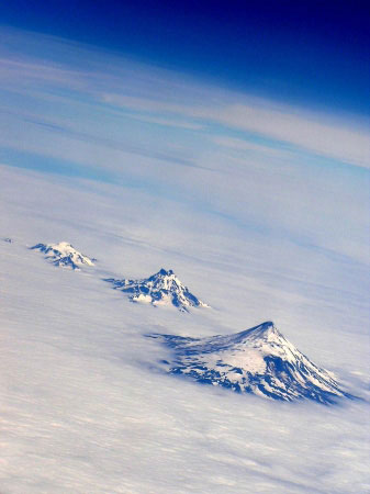 Roundtop Volcano (left), Isanotski Volcano (center), and Shishaldin Volcano (right) in Alaska